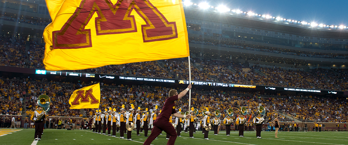 Minnesota Spirit Initiative students on the TCF football field during a game with the marching band