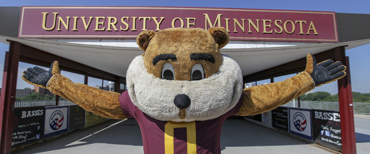 Goldy the Gopher standing with arms outstretched in front of UMN pedestrian bridge