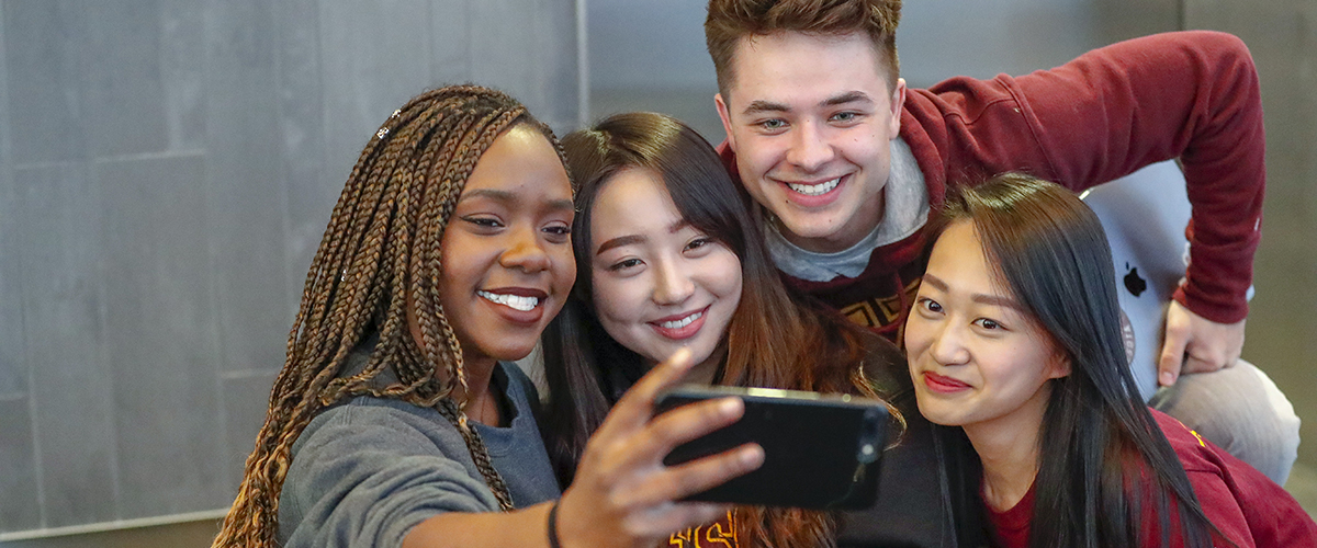 Four students gather to take a cell phone selfie