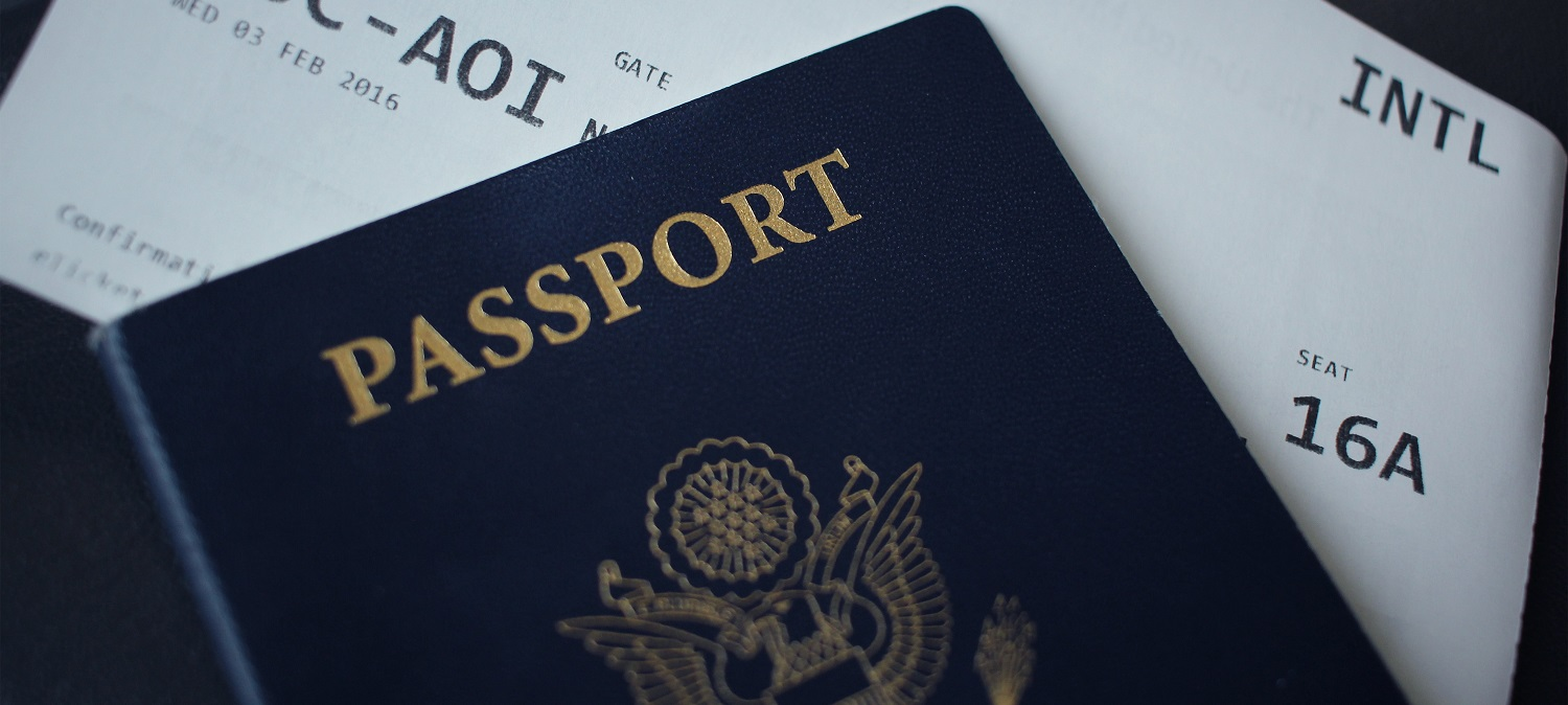 U.S. passport lying on top of a printed airline ticket