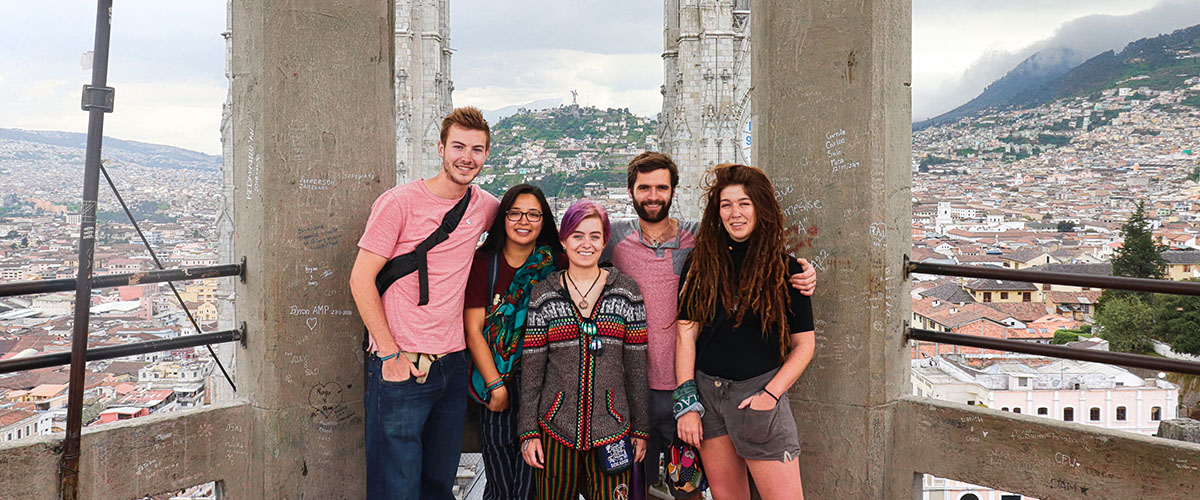 A group of five students stand atop the Quito, Ecuador bell tower