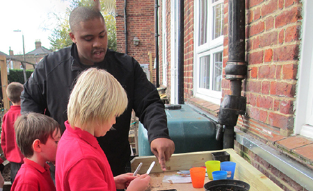 Student working with two school children in England