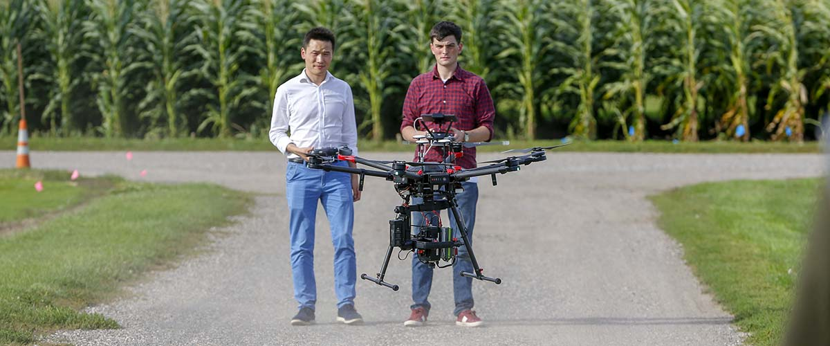 Two students stand side by side, with one operating a drone used for agricultural research.