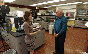 Food Science and Nutrition professor Gary Reineccius talks with WCCO reporter Heather Brown in a food science lab on campus.