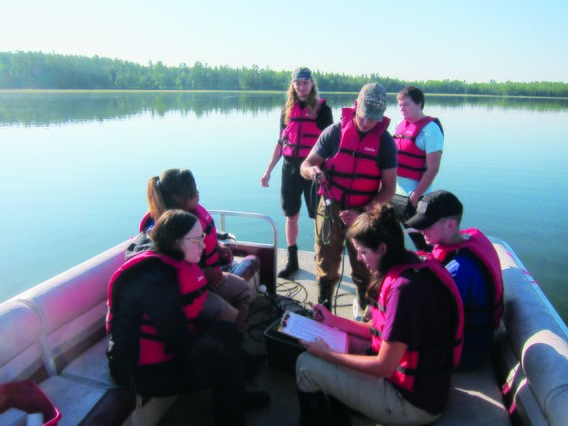 Seven students collect data while out on a boat wearing red life jackets