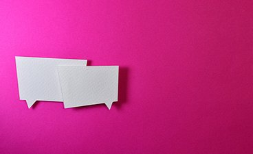 Two white cardboard conversation bubbles against a bright pink background