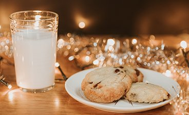 A glass of milk sits next to a plate of three chocolate chip cookies on a table decorated with twinkly lights and silver tinsel