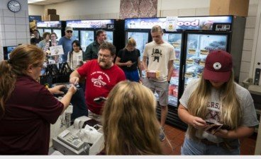 Cashiers manage a line of people waiting to pay for their selections at the meat and dairy sales room