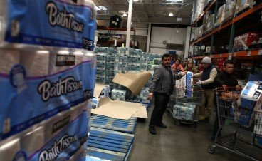 Customers wait in line with carts full of toilet paper at a retailer.