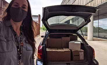 Bell Museum Public Science Events Manager Amber Kastner with a full vehicle of science kits.